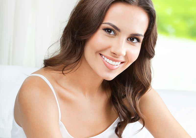 Krásna žena v bielom tielku s úsmevom