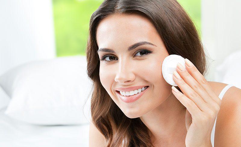 Usmiata žena s kozmetickým tampónom
