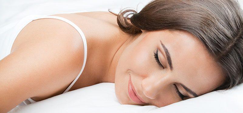 Žena spokojne spí na bielom vankúši