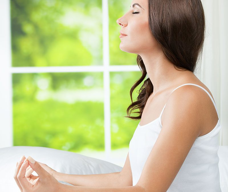 Žena v bielom tričku medituje